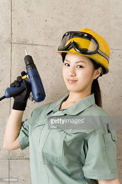 Female worker holding an electric drill, Side View