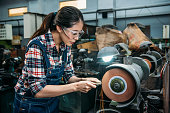 female worker holding components metal grinding