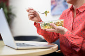 Female Worker In Office Having Healthy Pasta Lunch At Desk