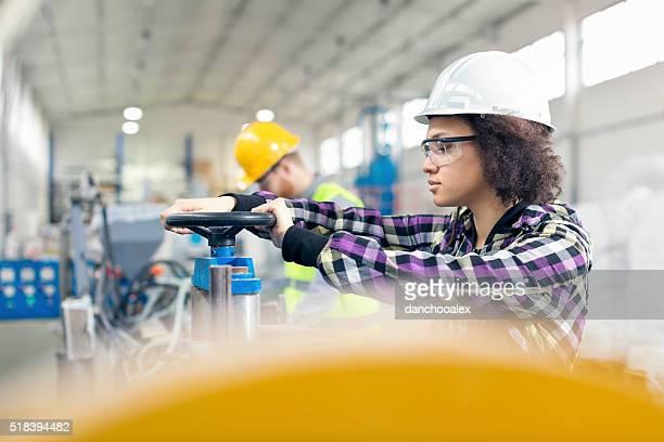 女性作業員は、工場に取り組んでいる、機