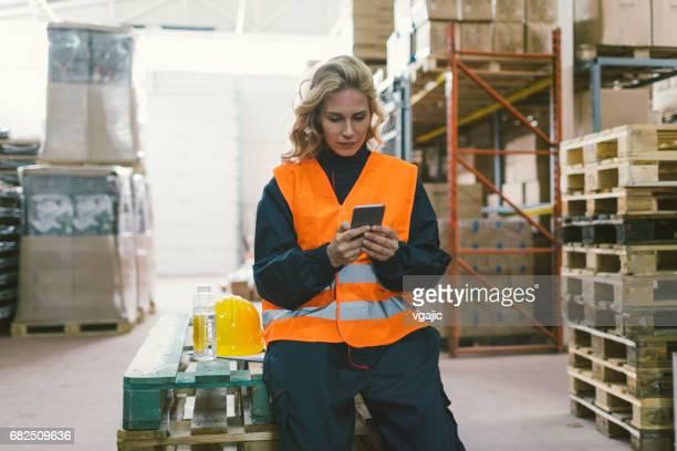 Female worker in warehouse using smart phone