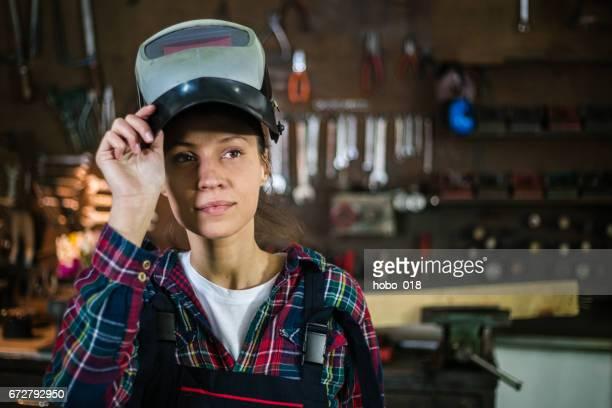 Female worker in workshop welding in car workshop