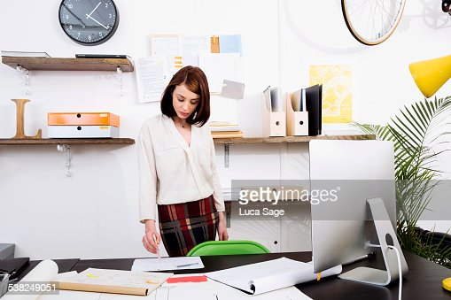 Female worker stands at her desk