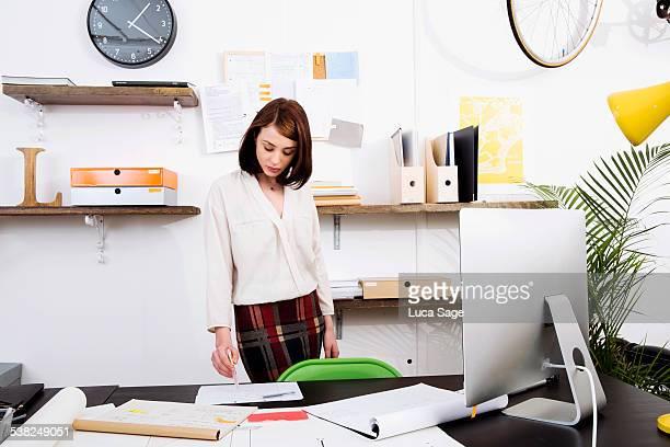 Female worker stands at her desk