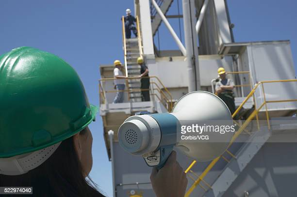 A female worker using a megaphone at an industrial facility