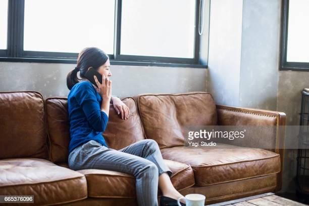 Female worker using a smart phone on sofa