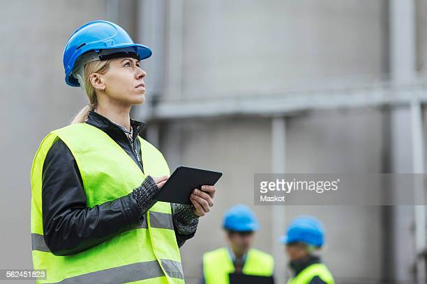 Female worker using digital tablet while looking away at factory