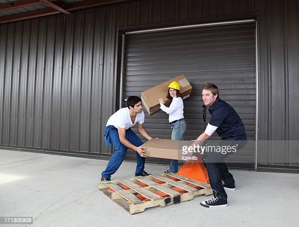 female worker watches two males struggling to lift small package