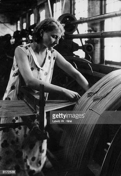 A female worker wearing a polkadotted dress stands over a loom warping velvet in a velvet factory