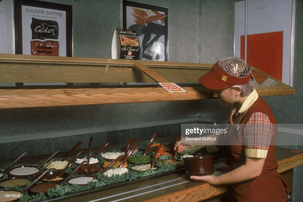 A female worker wears her uniform and a hairnet as she attends to the salad bar at a Burger King fast food restaurant, New York, August 1984.