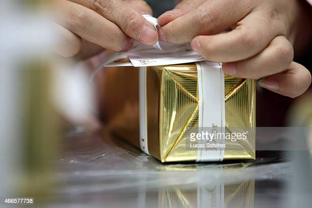 A female worker wraps a perfume in a box on the production line of Christian Dior perfumes' factory on November 9 2007 in Shanghai China