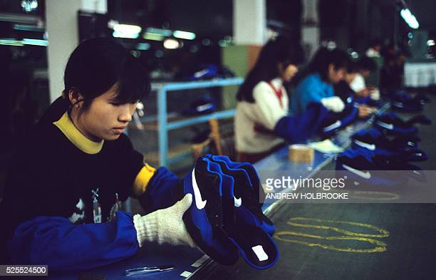 Female workers making sneakers on the assembly line at a Nike factory