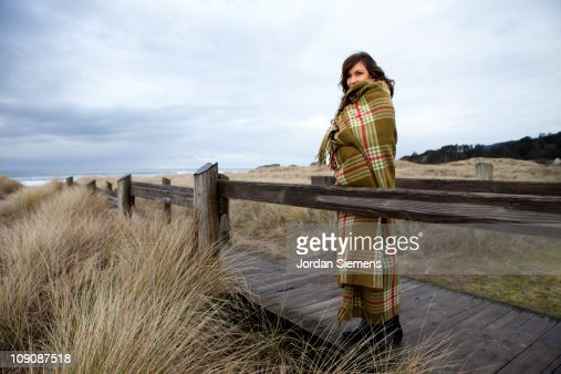 Female wrapped in blanket at beach. : ストックフォト