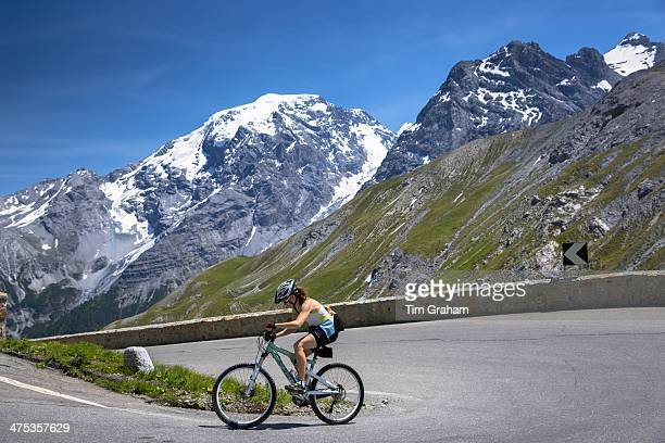 Female yclist rides Scott British mountain bike uphill on The Stelvio Pass Passo dello Stelvio Stilfser Joch in the Alps Italy