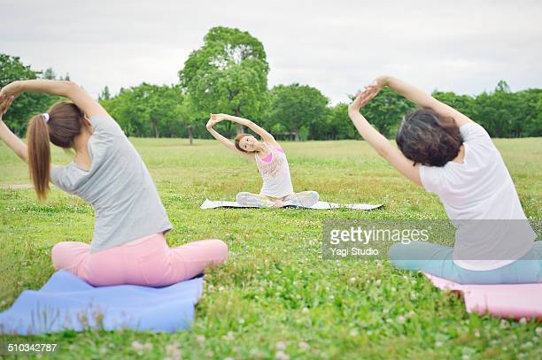 Female yoga instructor teaching yoga in park