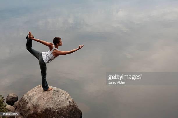 Female yogi practicing yoga on a rock by still water