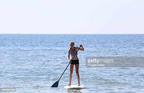 Female youth paddle boarding on the water