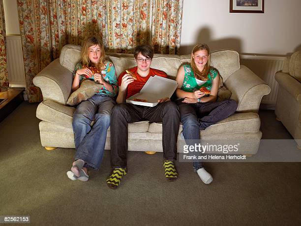 Females and male on sofa, eating pizza