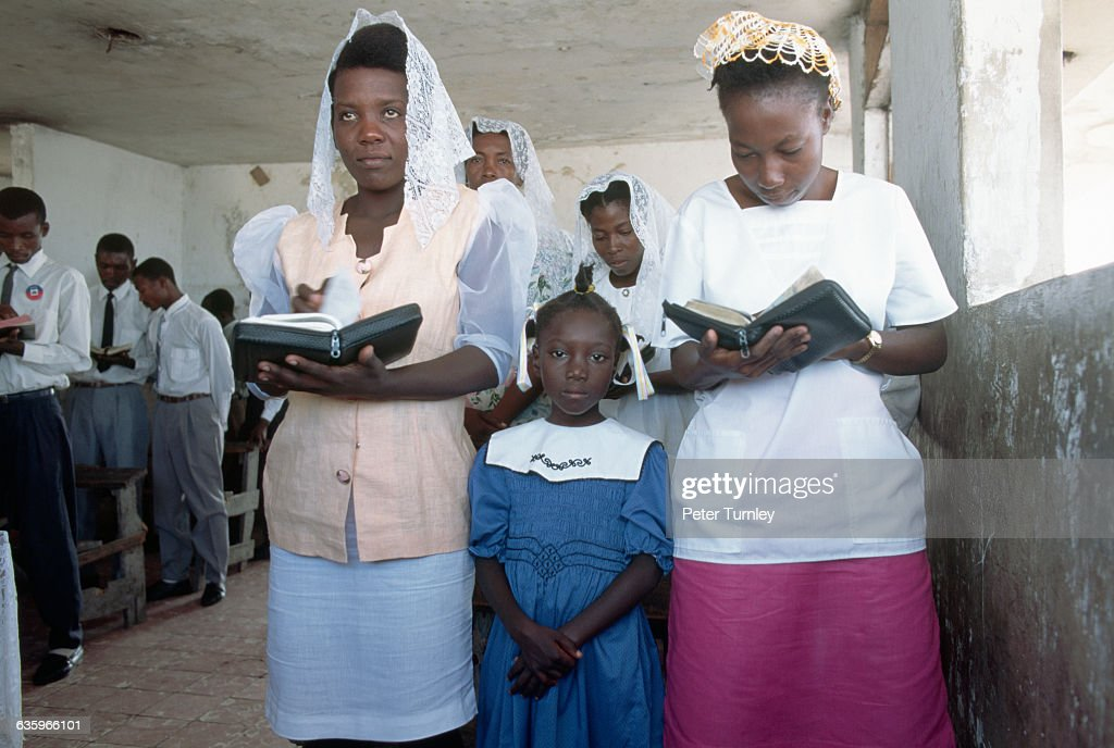Females and males stand on separate sides of a church during a service celebrating the return of exiled Haitian president Jean Bertrand Aristide