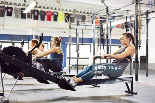 Females exercising on rowing machines in gym