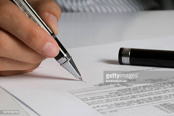 A females hand holding a pen and signing documents