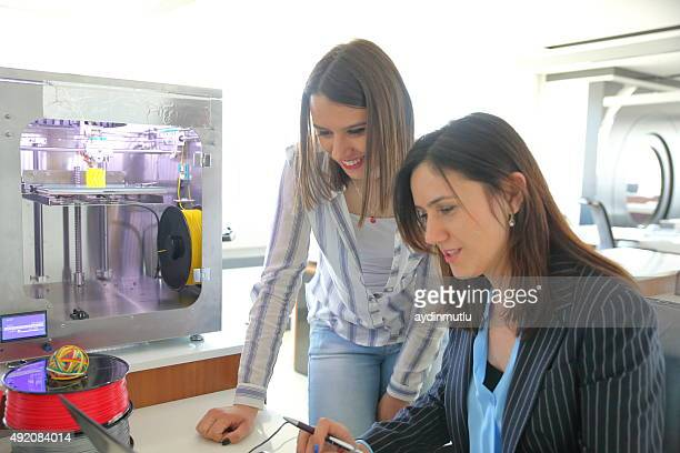Females working in 3D printer Office
