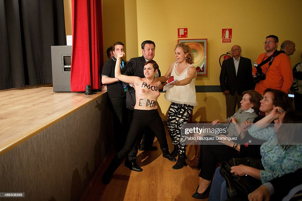 Femen activist tries to climb the stage as people hold her back during a speech of President of Madrid Popular Party Esperanza Aguirre at the...