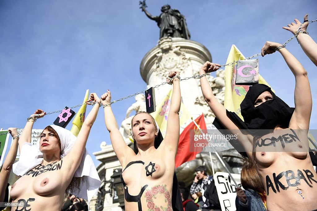 Femen leader <a gi-track='captionPersonalityLinkClicked' href=/galleries/search?phrase=Inna+Shevchenko&family=editorial&specificpeople=7249613 ng-click='$event.stopPropagation()'>Inna Shevchenko</a> (C) and other bare-chested activists of the feminist movement raise their hands symbolically chained together with religious signs as they take part in a parade marking International Women's Day in Paris on March 8, 2015.