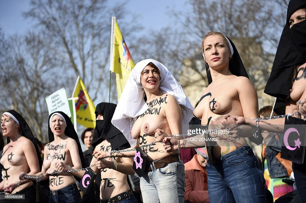 Femen leader <a gi-track='captionPersonalityLinkClicked' href=/galleries/search?phrase=Inna+Shevchenko&family=editorial&specificpeople=7249613 ng-click='$event.stopPropagation()'>Inna Shevchenko</a> (R) and other bare-chested activists of the feminist movement march with their hands symbolically chained together with religious signs as they take part in a parade marking International Women's Day in Paris on March 8, 2015.