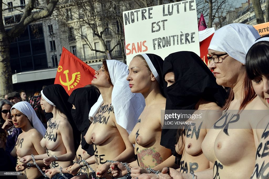 Femen leader <a gi-track='captionPersonalityLinkClicked' href=/galleries/search?phrase=Inna+Shevchenko&family=editorial&specificpeople=7249613 ng-click='$event.stopPropagation()'>Inna Shevchenko</a> (C) and other bare-chested activists of the feminist movement stand with their hands symbolically chained together with religious signs as they take part in a parade marking International Women's Day in Paris on March 8, 2015.