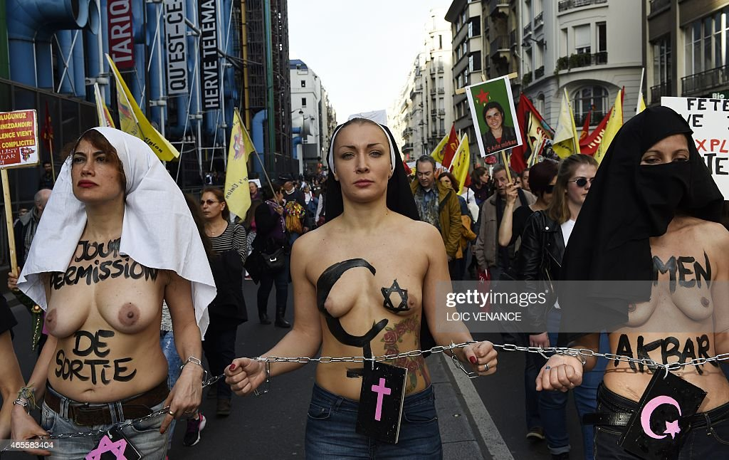 Femen leader <a gi-track='captionPersonalityLinkClicked' href=/galleries/search?phrase=Inna+Shevchenko&family=editorial&specificpeople=7249613 ng-click='$event.stopPropagation()'>Inna Shevchenko</a> (C) and other bare-chested activists of the feminist movement march with their hands symbolically chained together with religious signs as they take part in a parade marking International Women's Day in Paris on March 8, 2015. AFP PHOTO / LOIC VENANCE