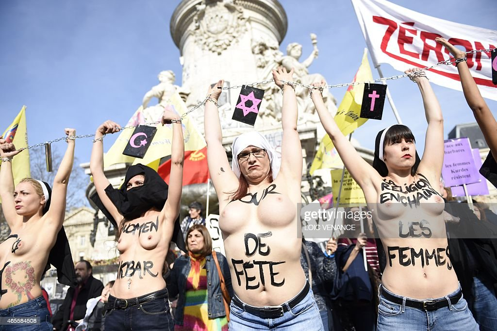 Femen leader <a gi-track='captionPersonalityLinkClicked' href=/galleries/search?phrase=Inna+Shevchenko&family=editorial&specificpeople=7249613 ng-click='$event.stopPropagation()'>Inna Shevchenko</a> (R) and other bare-chested activists of the feminist movement raise their hands symbolically chained together with religious signs as they take part in a parade marking International Women's Day in Paris on March 8, 2015.
