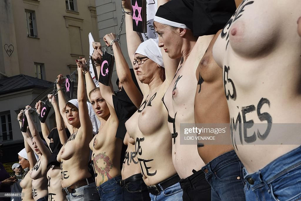 Femen leader <a gi-track='captionPersonalityLinkClicked' href=/galleries/search?phrase=Inna+Shevchenko&family=editorial&specificpeople=7249613 ng-click='$event.stopPropagation()'>Inna Shevchenko</a> (C) and other bare-chested activists of the feminist movement raise their hands symbolically chained together with religious signs as they take part in a parade marking International Women's Day in Paris on March 8, 2015. AFP PHOTO / LOIC VENANCE