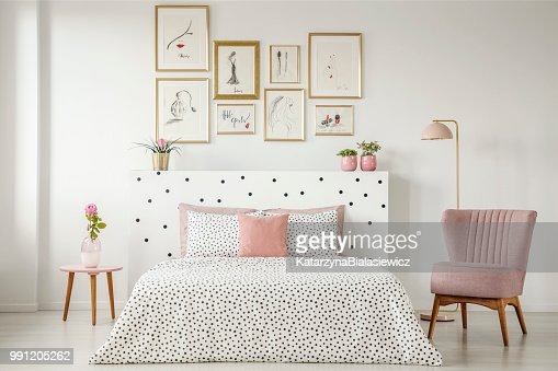 Feminine bedroom interior with a double bed with dotted sheets, armchair, art collection and plants : Stock Photo