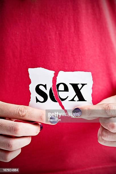 "Feminine hand rips up sign saying ""sex"""