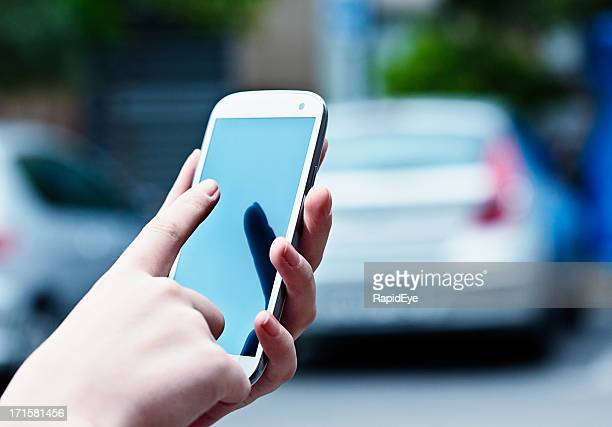 Feminine hands touch blank screen of unbranded mobile phone