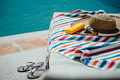 Selection of womens items by a pool. There is a colourful towel on the deck chair with a sunhat, sunglasses and sun lotion and some flip flops.