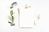 Feminine stationery, desktop mock-up scene. Blank greeting card, craft envelope, washi tape and golden paper, binder clips with olive branch, white table background. Flat lay, top view.