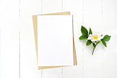 Feminine wedding stationery, floral desktop mock-up scene. Blank greeting card, craft envelope and blooming wild rose branch. Old white wooden table background, lat lay, top view.