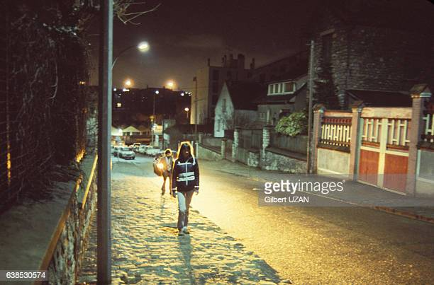 Femme marchant dans la rue de nuit dans les années 1980 à Paris France