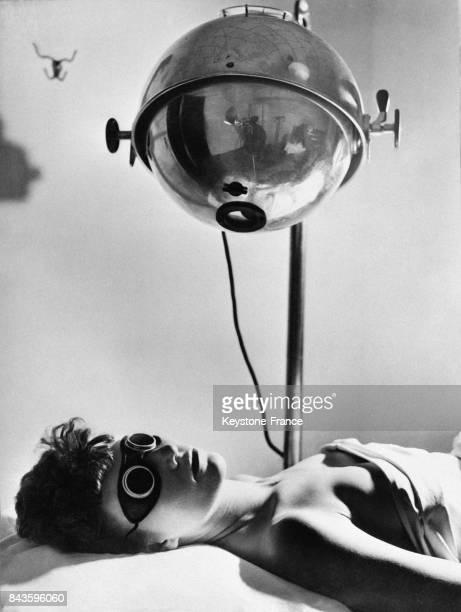 Femme munie d'un bandeau sur les yeux est allongée sous une lampe ultraviolet aux EtatsUnis en 1946