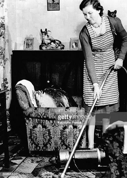 Femme passant l'aspirateur dans son salon circa 1940
