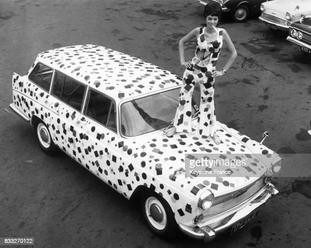 Femme portant des vêtements bariolés et des motifs assortis à la peinture de la carrosserie de sa voiture à Londres RoyaumeUni le 13 septembre 1967