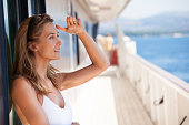 belle femme blonde sur le pont d'un bateau regardant l'horizon