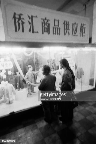 Femmes devant la vitrine d'un magasin de vêtements à Shanghai en février 1979 en Chine