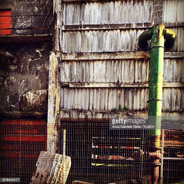 Fence By Green Pipe At Old Building