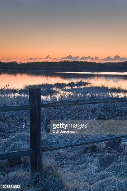 Fence by lake at sunset