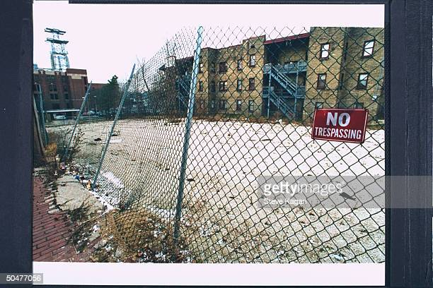 Fencebordered vacant lot sporting a NO TRESSPASSING sign formerly the site of the apartment bldg where serial killer cannibal Jeffrey Dahmer resided...