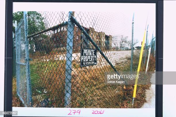 Fencebordered vacant lot sporting a PRIVATE PROPERTY NO TRESSPASSING sign formerly the site of the apartment bldg where serial killer cannibal...