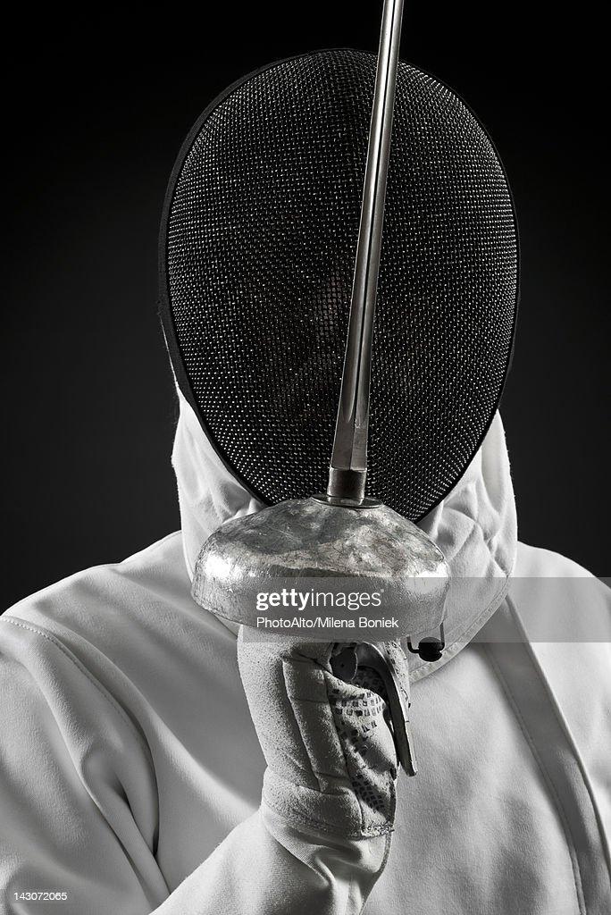 Fencer holding up foil, portrait : Stock Photo